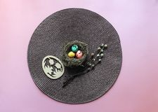 On a pink background eggs quail in a nest red yellow green color willow branches blossom round napkin brown wooden egg batch royalty free stock photos