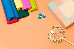On a pink background is a gift box, packing colored corrugated paper and colorful plastic and wooden hearts royalty free stock photo