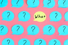 On a pink background many blue stickers with question marks are glued. One of the stickers is yellow , with the question. WHAT . An unusual bright photo Royalty Free Stock Photo