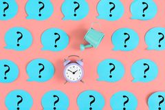 On a pink background, many blue stickers with question marks are pasted. Among them, a alarm clock and a blue watering royalty free stock image