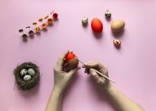 On a pink background with a paint egg chicken and quail nest with three quail eggs red and orange color hand paint paint egg red Royalty Free Stock Image