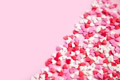 Pink background and many sugar red,pink hearts. Pink background and pink red sweet sprinkling hearts poured diagonal background Stock Photography