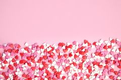 Pink background and many sugar red,pink hearts. Pink background and pink red sweet sprinkling hearts poured horizontally background Royalty Free Stock Image