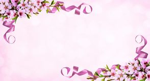 Pink background with spring twigs of peach flowers and silk ribb. Spring twigs of peach flowers and silk ribbon corner arrangements on pink bokeh background Royalty Free Stock Photography