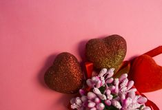 Pink background. St. Valentine`s Day. Red hearts in spangles with bows. Love. Bouquet of flowers. The place for an inscription. stock photo