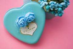 Pink background. St. Valentine`s Day. Turquoise. A box in the form of heart of blue color. Love. Flowers. Romance. Congratulation. Pink background. St royalty free stock images