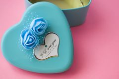 Pink background. St. Valentine`s Day. Turquoise. A box in the form of heart of blue color. Love. Flowers. Romance. Congratulation. Pink background. St stock photography