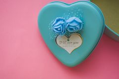 Pink background. St. Valentine`s Day. Turquoise. A box in the form of heart of blue color. Love. Flowers. Romance. Congratulation. Pink background. St stock images