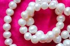 Pearl Necklace. Pink background with white pearls. Beautiful texture stock photo