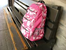 Pink Backpack. On wooden bench at school Stock Photos