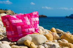 Pink bag on a pebble beach. Modern pink bag on a pebble beach with a blue sea and a blue sky in the background Stock Photo