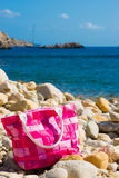 Pink bag on a pebble beach. Modern pink bag on a pebble beach with a blue sea and a blue sky in the background Royalty Free Stock Photos