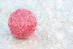 Pink ball on glitter. Pink sparkly christmas decoration ball on white glitter great for backgrounds, name tags or greeting card royalty free stock photo