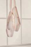 Pink ballet pointe shoes hanging on window Royalty Free Stock Photos