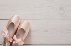 Pink ballet pointe shoes on white wood background. Pastel pink ballet shoes background. New pointe shoes with satin ribbon lay on white rustic shubby chic wood Royalty Free Stock Images