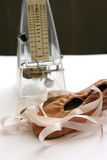 Pink ballet shoes, metronome. A pair of soft pink ballet shoes for little children, with long pink ribbons for tying.  Placed next to a ticking metronome of a Stock Image