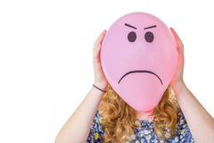 Pink balloon with facial expression in front of girls face Royalty Free Stock Images