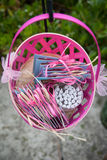 Pink basket. A pink basket with blue cards and candles inside hanging from a hook Stock Photos