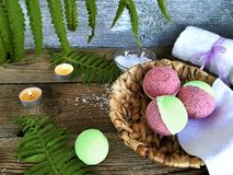 Pink bath bombs in basket with fern leaves  on wooden background. royalty free stock images