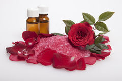Pink bath salt in rose petals and bottles with oil Stock Photo