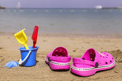 Pink beach crocs and blue sand toys on sandy beach.Beach flip flops in the foreground and blurred sea in the background Stock Photography