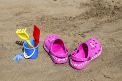 Pink beach crocs and blue sand toys on sandy beach.Beach flip flops in the foreground and blurred sea in the background Stock Images
