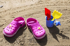 Pink beach crocs and blue sand toys on sandy beach.Beach flip flops in the foreground and blurred sea in the background Stock Photo