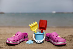 Pink beach crocs and blue sand toys on sandy beach.Beach flip flops in the foreground and blurred sea in the background Royalty Free Stock Photography