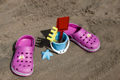 Pink beach crocs and blue sand toys on sandy beach.Beach flip flops in the foreground and blurred sea in the background.  Stock Photography