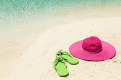 Pink beach hat and green slippers in the golden sand by sea shor Royalty Free Stock Image