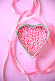 Pink beads in heart pan on polka dots Stock Image