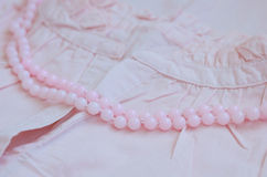 Pink beads over vintage womans cotton dress Stock Image