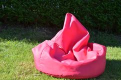 Pink bean bag. On a garden lawn royalty free stock photo