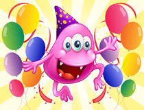 A pink beanie monster in the middle of the balloons Stock Photo