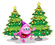 A pink beanie monster near the green christmas trees Royalty Free Stock Photos