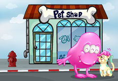 A pink beanie monster and a pet in front of the pet shop Stock Images