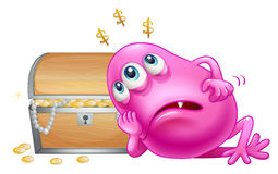 A pink beanie monster beside the treasure box Stock Photos