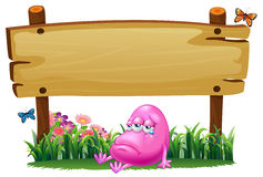 A pink beanie monster under the empty wooden signboard Stock Image