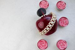 A pink beautiful glass transparent bottle of female perfume adorned with white drab pearls and pink paraffin candles in the shape. Of a rose and place for a royalty free stock images