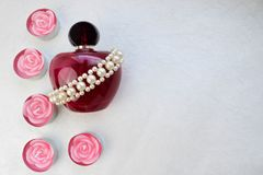 A pink beautiful glass transparent bottle of female perfume adorned with white drab pearls and pink paraffin candles in the shape. Of a rose and place for a stock image