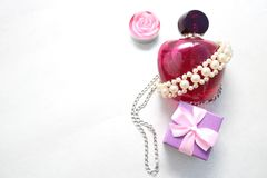 Pink beautiful glass transparent bottle of female perfume decorated with white pearls and a candle in the form of a rose blue smal. L gift box and place for a Stock Images