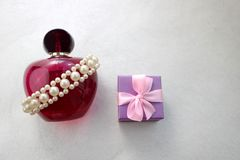 Pink beautiful glass transparent bottle of female perfume decorated with white precious pearls and blue small gift box and place f Stock Images