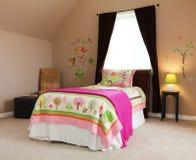 Pink bed in kids baby girl bedroom interior. Pink bed in kids baby girl bedroom interior with brown walls Stock Photography