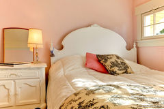 Pink bedroom with white bed and night stand. Stock Photography