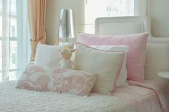 Pink and beige pillows on bed next to window Royalty Free Stock Photos