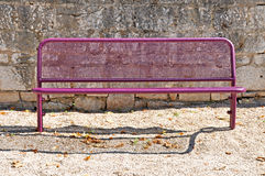 Pink bench. And a stone wall stock images