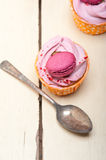 Pink berry cream cupcake with macaroon on top Stock Images