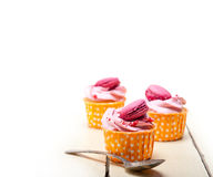 Pink berry cream cupcake with macaroon on top Royalty Free Stock Photography