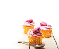Pink berry cream cupcake with macaroon on top Stock Photo