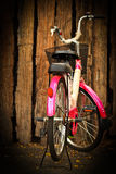 Pink bicycle. With old  wood background Royalty Free Stock Photos